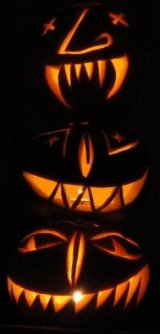 Three jack-o'-lanterns illuminated from within by candles.